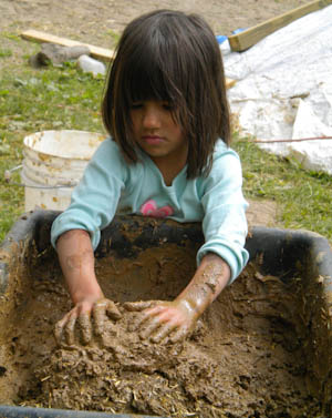 Kindergartner mixing the mud plaster.