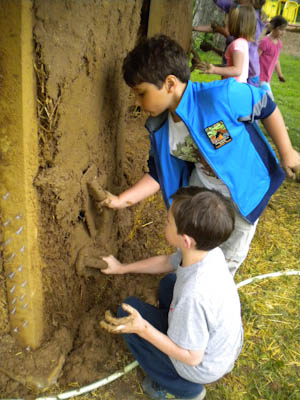 Two Younger Group children work together to plaster a playhouse wall.
