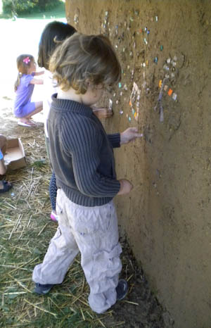 Kindergartner adds to the mosaics on a playhouse wall.