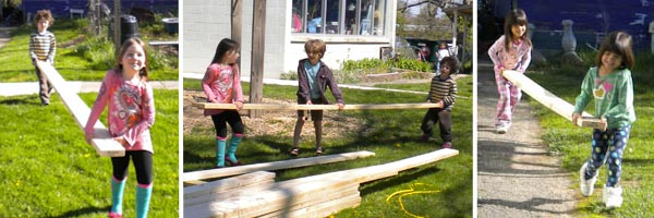 Kindergartners carry lumber for the playhouse.