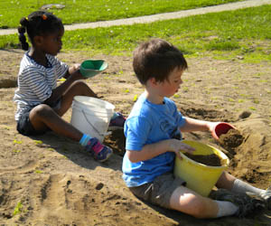 Nursery children dig sand for the foundation.