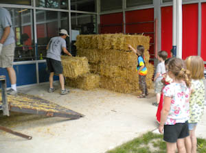 Children supervise the unloading of the straw.