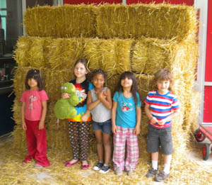Some Kindergartners beside the straw that will be the playhouse walls.