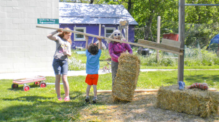 Children help compact a straw bale with some guidance from Beth