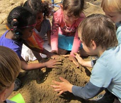 Nursery children bury dead bird/